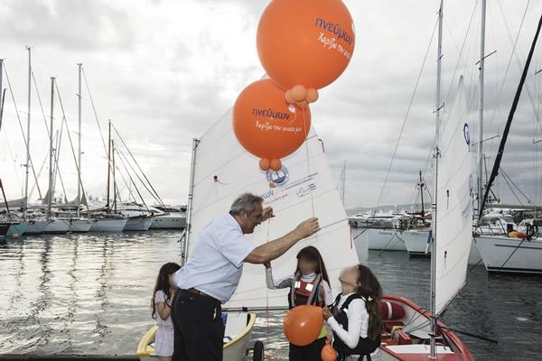 Ο κ. Μιχάλης Τουμπής, Πρόεδρος της Ε.Π.Ε., παραδίδει τα δύο μπαλόνια στις μικρές ιστιοπλόους